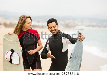 Surfers family on the beach in wetsuits - stock photo