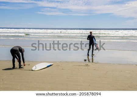Surfers on a Beach Getting Ready to Ride the Surf