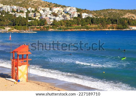 Surfers on calm waves on the shores of the Aegean sea, Vouliagmeni, Greece - stock photo