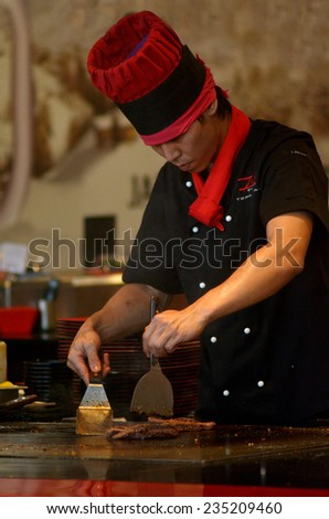 SURFERS PARADISE, AUS - NOV 10 2014:A teppanyaki chef cooking at a gas powered teppan in a Japanese steakhouse.is a style of Japanese cuisine that uses an iron griddle to cook food. - stock photo