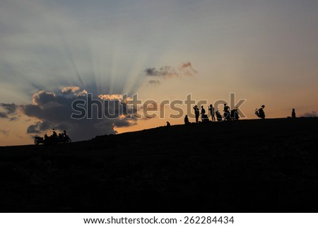 Surfers silhouettes on sunset background - stock photo