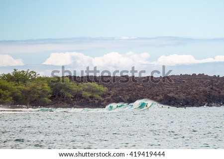 Surfers Surfing Large Waves on a Tropical Island - stock photo
