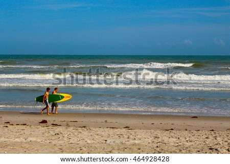 Surfers walking down a beach