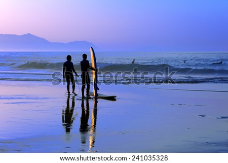 surfers with sunset reflection on the surfboard - stock photo