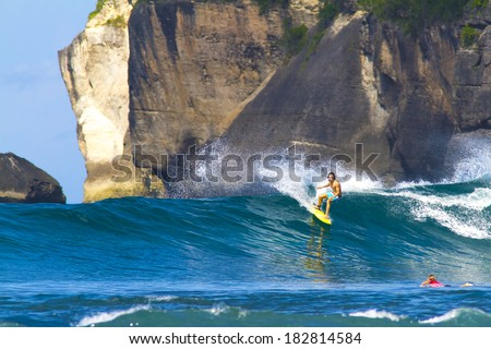 surfing a wave in Indonesia - stock photo