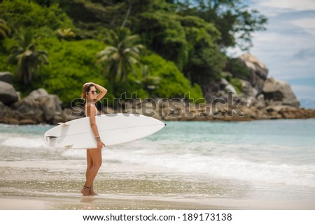 Surfing beach woman. Happy surfer girl running laughing cheerful having fun with bodyboarding surfboard on summer holidays vacation travel on Tropical ocean beach - stock photo