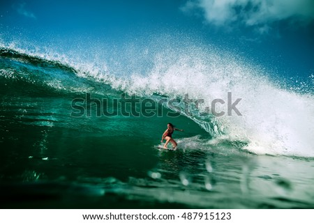 Surfing girl riding a giant ocean wave. Blue ocean water crashing with splashes and drops. Water sport activity