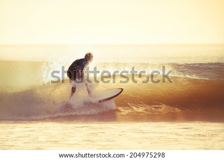 Surfing in the early morning with filter effect applied. - stock photo