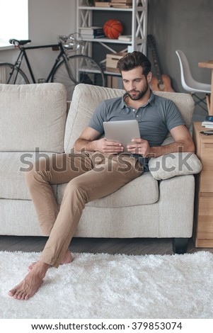 Surfing net at home. Handsome young man using his digital tablet while sitting on the couch at home - stock photo