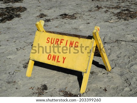 Surfing only sign on the beach