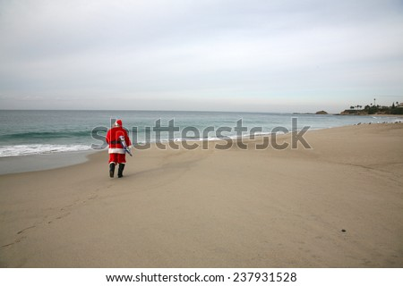 Surfing Santa Claus. A lonely Santa Claus walks on an empty beach with his Surfboard under his arm ready to go ride the waves alone. Reindeer and Elves do not surf so they leave Santa alone.   - stock photo
