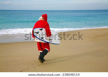 Surfing Santa Claus. Santa Claus holds his Blue Surfboard under his arm as he checks out the Waves at one of his Favorite Secret Surfing Spots. Santa loves Sports and Surfing. They call him Mr. Claus  - stock photo