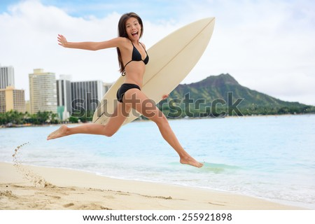 Surfing surfer happy having fun with surfboard jumping funny making excited face expression. Female bikini woman healthy active water sport lifestyle. Asian Caucasian model on Waikiki, Oahu, Hawaii. - stock photo