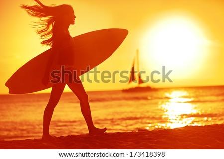 Surfing surfer woman babe beach fun at sunset. Girl walking in sunshine in warm evening sun holding surfboard. Water sport summer vacation travel concept. Kaanapali beach, Maui, Hawaii, USA - stock photo