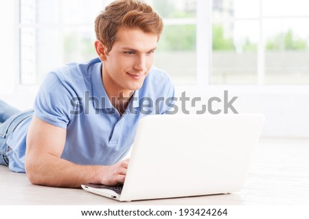 Surfing the net at home. Handsome young man working on laptop while lying on the floor at his apartment - stock photo