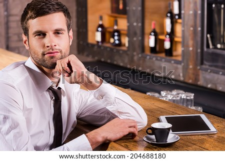 Surfing the net in bar. Handsome young man in shirt and tie holding hand on chin and smiling while sitting at the bar counter with digital tablet laying near him - stock photo