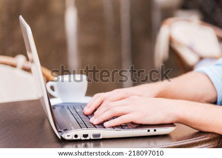 Surfing the net in cafe. Close-up of man working on laptop while sitting in sidewalk cafe - stock photo