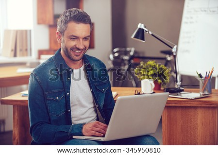 Surfing the net in office. Confident young man working on laptop and smiling while sitting at his working place in office - stock photo