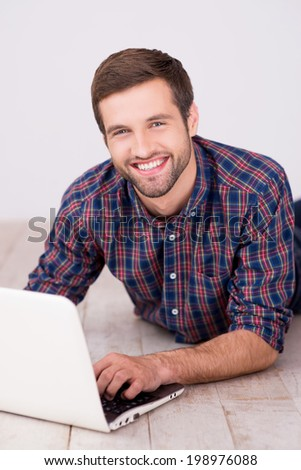Surfing the net is fun. Handsome young man working on laptop and smiling while lying on hardwood floor - stock photo