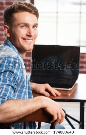 Surfing the net is fun. Rear view of handsome young man looking over shoulder and smiling while sitting at his working place  - stock photo