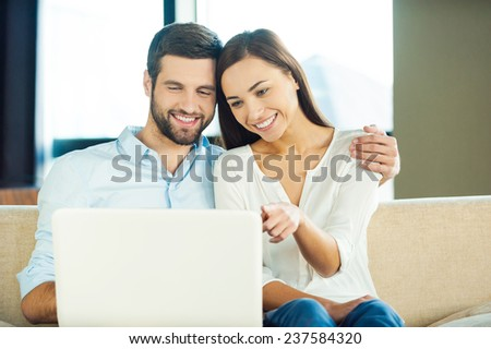Surfing the net together. Beautiful young loving couple sitting together on the couch and looking at laptop