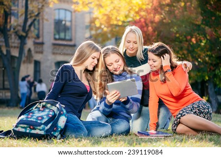 Surfing the net together. Four happy young caucasian woman looking at tablet pc and smiling while  they rest on grass at campus together - stock photo