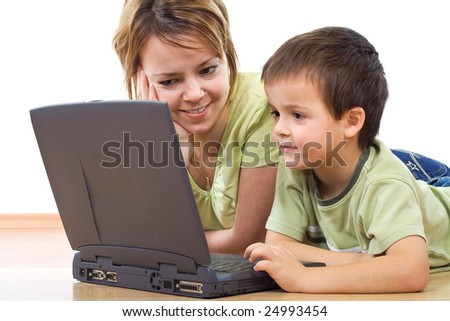 Surfing the web - woman and little boy laying on the floor with a laptop - isolated