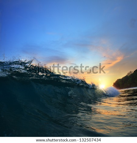 Surfing tropical design template. Green blue colored ocean wave breaking and splashing at sunset time - stock photo