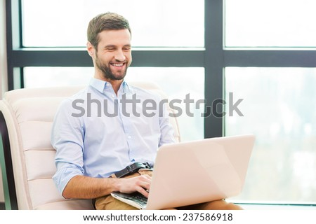 Surfing web at home. Handsome young man working on laptop and smiling while sitting at the chair at home - stock photo