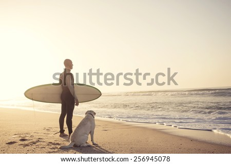 Surfist on the beach with his best friend - stock photo