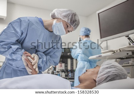 Surgeon consulting a patient and holding hands - stock photo