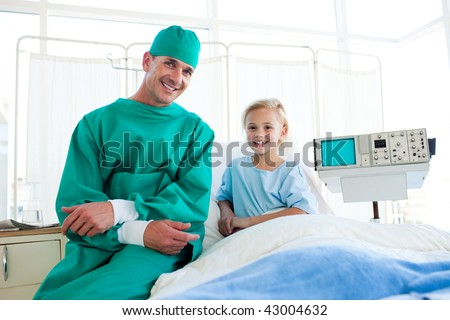 Surgeon explaining a surgery to a little girl in a hospital - stock photo