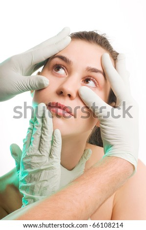 Surgeon gloves above woman face for plastic surgery, beauty treatment - stock photo