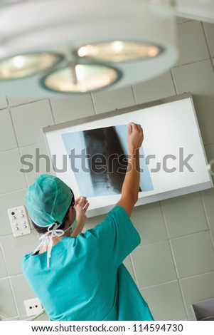 Surgeon holding a x-ray in a surgical room - stock photo