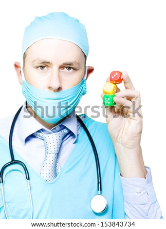 Surgeon in mask and gown holding up a set of three colourful dice in a surgery risk, probability and chance, or dicing with death concept - stock photo