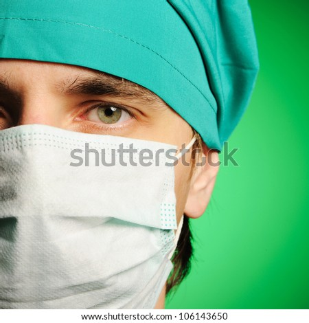 Surgeon in mask over green - stock photo