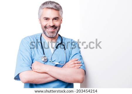Surgeon leaning at copy space. Confident mature surgeon leaning at copy space and smiling while standing isolated on white - stock photo