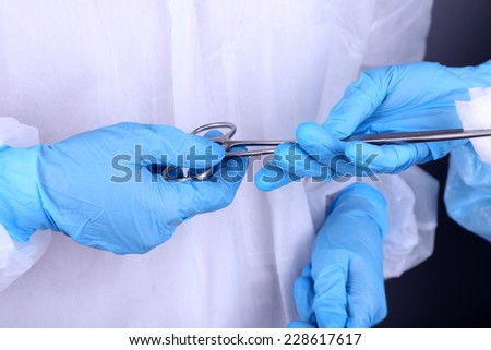 Surgeon's hands holding clip with napkin close up