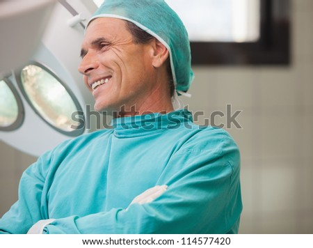 Surgeon smiling with arms crossed in operating theatre in hospital - stock photo