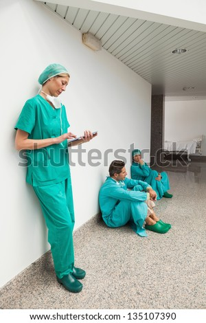 Surgeon using tablet computer in hospital corridor with two surgeons sitting on floor - stock photo