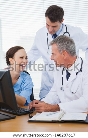 Surgeon working with doctors on computer in bright office