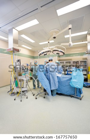 Surgeons operating patient in operation room