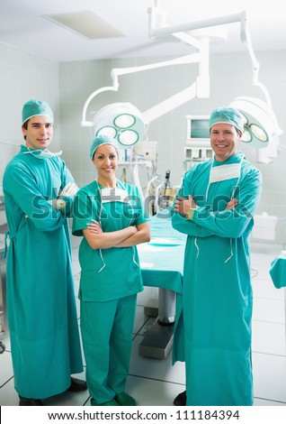 Surgeons smiling with arms crossed in an operating theater