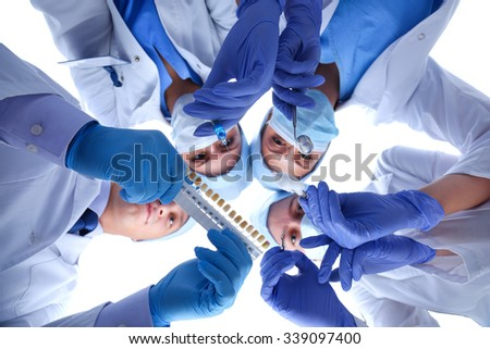 Surgeons team, man and woman wearing protective uniforms,caps and masks - stock photo