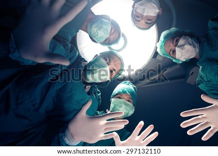 Surgeons team standing above of the patient before surgery - stock photo