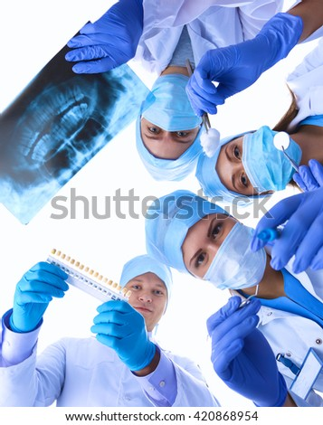 Surgeons team,  woman wearing protective uniforms,caps and masks - stock photo