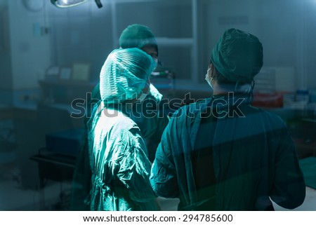 Surgery team speaking to each other at operating room - stock photo