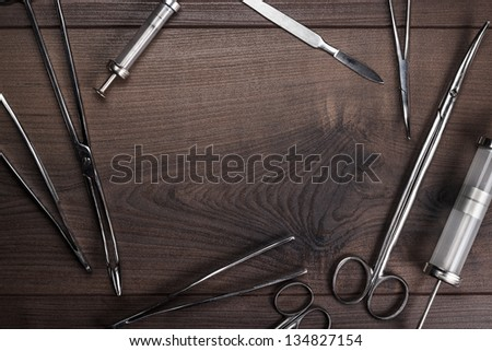 surgical armaments on the brown wooden table background - stock photo