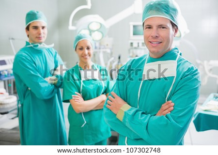 Surgical team smiling with arms crossed in an operating theatre - stock photo
