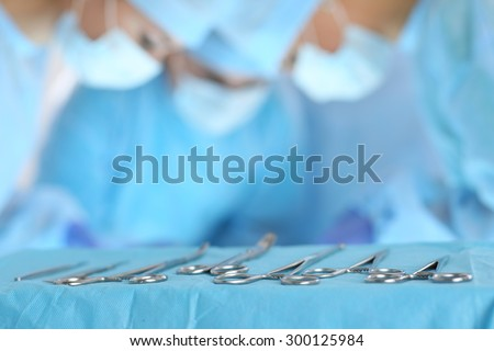 Surgical tools lying on table while group of surgeons at background operating patient in surgical theatre. Steel medical instruments ready to be used. Surgery and emergency concept - stock photo